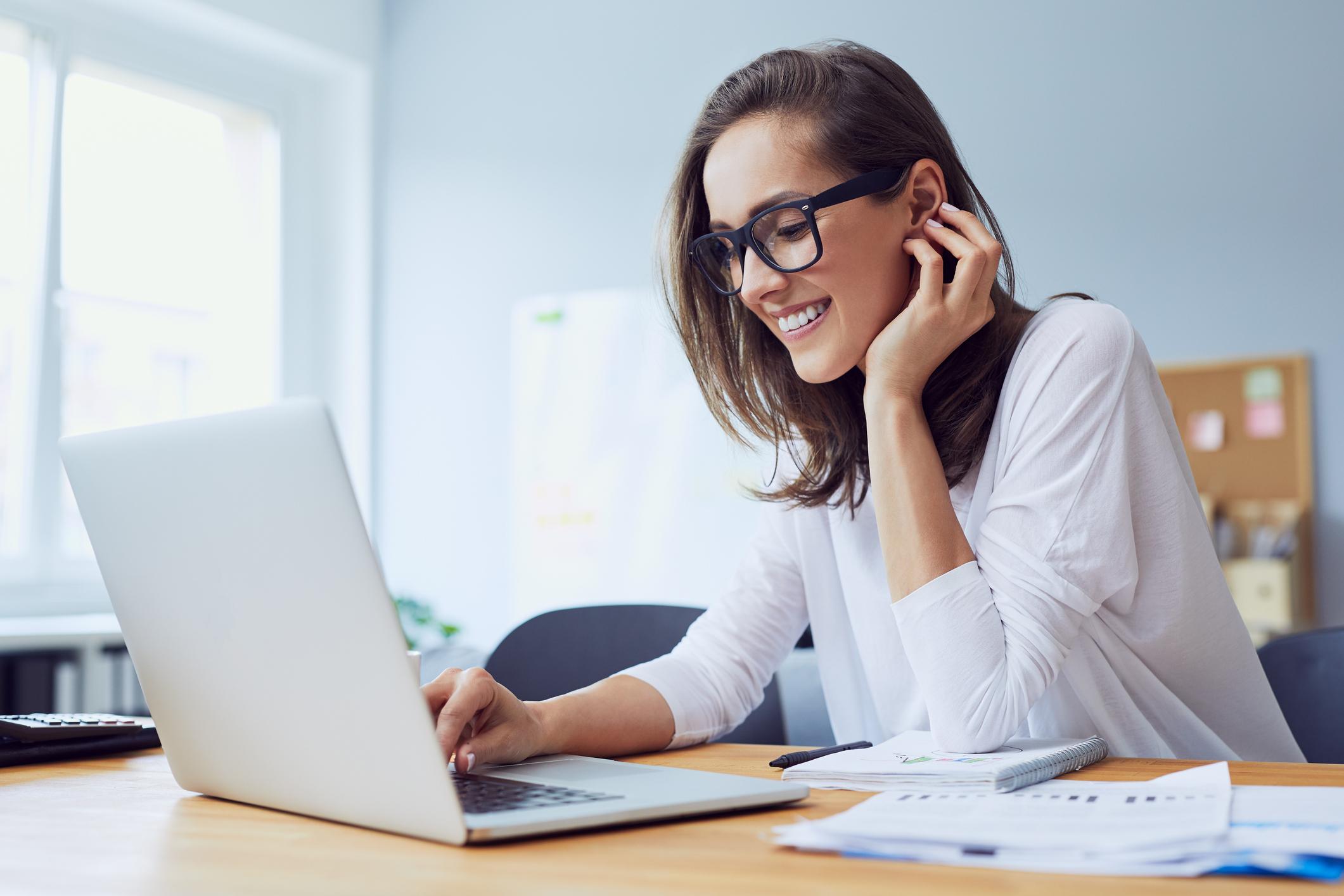 Une femme souriante en face de son ordinateur